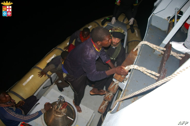 This handout picture released on April 8, 2014 by The Marina Militare shows rescuers of the Italian Navy helping refugees to climb on their boat near the Italian port of Pozzallo, south of Sicily.