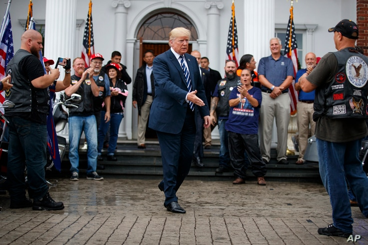 President Donald Trump greets members of Bikers for Trump and supporters, Saturday, Aug. 11, 2018, at the clubhouse of Trump National Golf Club in Bedminster, N.J.