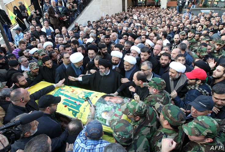 Lebanese Shiite cleric and senior Hezbollah offical Hashim Safi al-Din, center, stands with fellow mourners during a funeral procession in a southern suburb of the Lebanese capital Beirut, Dec. 21, 2015.