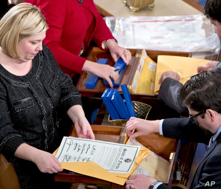 FILE - clerks unseal the certificates of results from all fifty states during a meeting of the U.S. Electoral College in the House of Representatives on Capitol in Washington.