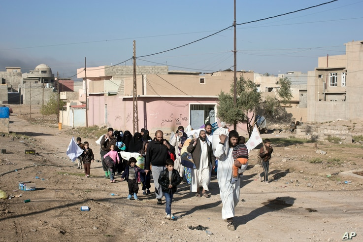 People displaced by fighting between the Iraqi military and Islamic State militants pass through an alley in Gogjali, on the eastern outskirts of Mosul, Iraq, Nov. 5, 2016. Mosul is the last major IS stronghold in Iraq.