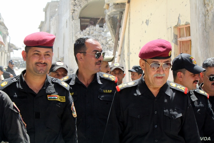 Major Assad al-Assadi (L) and Lt. General Abdul Ghani al-Assadi (R) of Iraqi Special Forces, or the Golden Division, tour areas of the Old City they captured in recent days, now abandoned and in ruins on June 22, 2017 in Mosul, Iraq. (H.Murdock/VOA)
