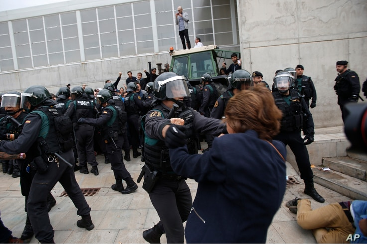 Civil guards clear people away from the entrance of a sports center, assigned to be a polling station by the Catalan government in Sant Julia de Ramis, near Girona, Spain, Oct. 1, 2017.