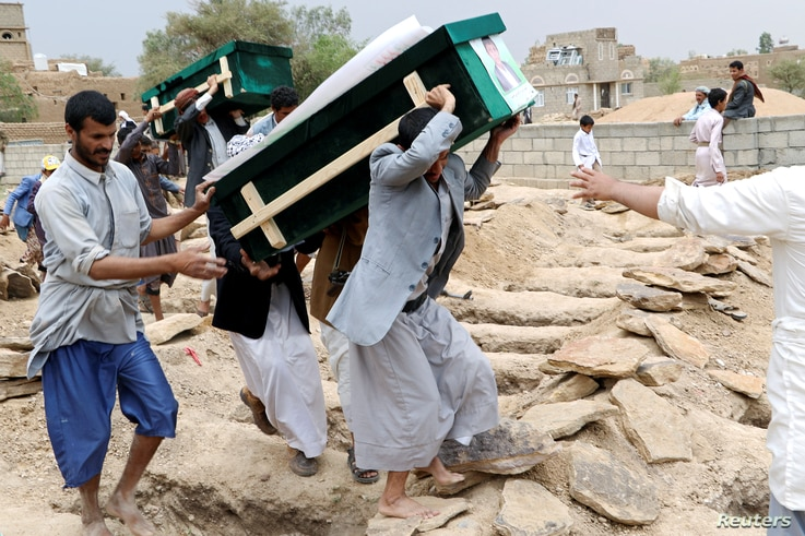 Mourners carry coffins during a funeral of people, mainly children, killed in a Saudi-led coalition air strike on a bus in northern Yemen, in Saada, Yemen August 13, 2018.
