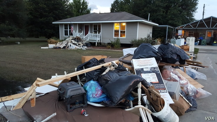 Residents of St. Amant, La., clear flood-damaged household goods out of their homes, Aug. 22, 2016.
