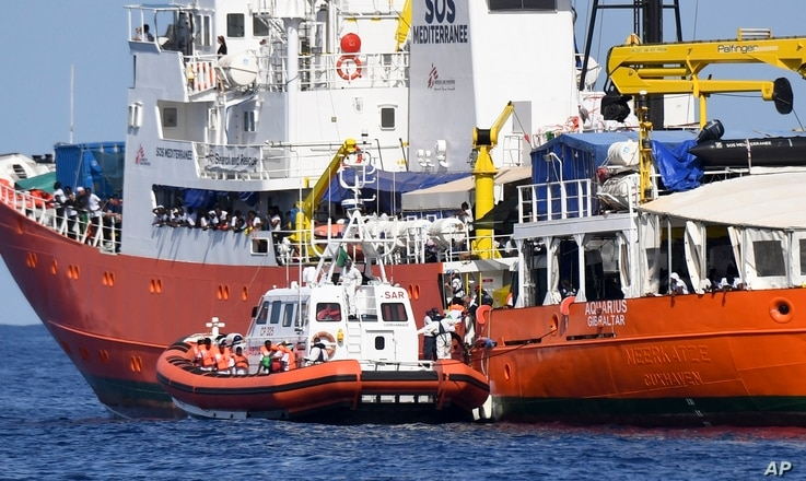 "An Italian Coast Guard boat approaches the French NGO ""SOS Mediterranee"" Aquarius ship as migrants are being transferred, in the Mediterranean Sea, June 12, 2018."