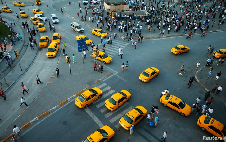 FILE - Yellow taxis pass people standing at Taksim Square, in Istanbul, Turkey, June 19, 2013.