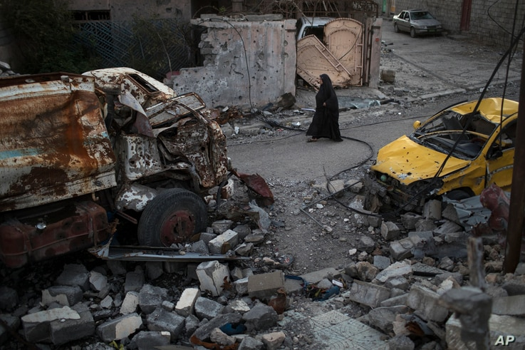A woman walks past damaged vehicles in a neighborhood recently retaken by Iraqi security forces from Islamic State militants, in west Mosul, Iraq, April 5, 2017.