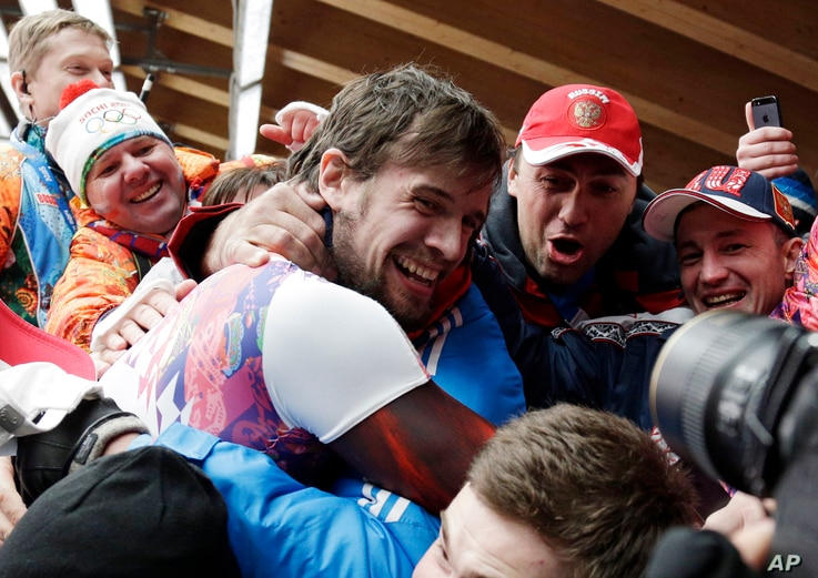 Alexander Tretiakov of Russia celebrates with fans and supporters in the finish area after he won the gold medal during the men's skeleton competition at the 2014 Winter Olympics, Saturday, Feb. 15, 2014, in Krasnaya Polyana, Russia.  (AP Photo/Micha...