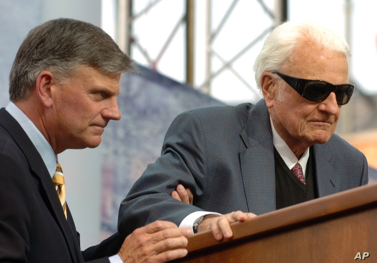 Evangelist Billy Graham, right, is assisted by his son Franklin before delivering a sermon during the Metro Maryland Festival,July 9, 2006, in Baltimore.