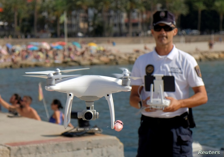 Local police officer Agustin Mirete controls a drone equipped with a camera used for surveillance tasks in the Poniente beach at the eastern costal town of Benidorm, Spain, Aug. 18, 2016.
