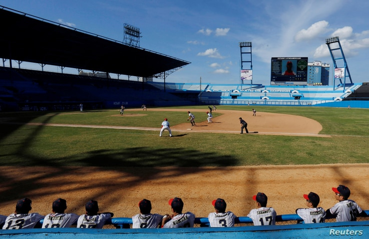 Japan's national youth baseball team players (back to camera) watch a friendly game against Cuba at the Latinoamericano stadium in Havana, Cuba, Dec. 19, 2018.