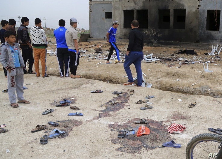 People inspect the aftermath of a suicide bombing at a soccer field in Iskandariya, 25 miles (about 40 kilometers) south of Baghdad, Iraq, March 26, 2016.