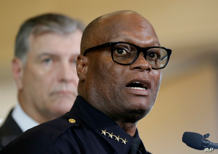 Dallas police chief David Brown, front, and Dallas mayor Mike Rawlings, rear, talk with the media during a news conference, July 8, 2016, in Dallas.