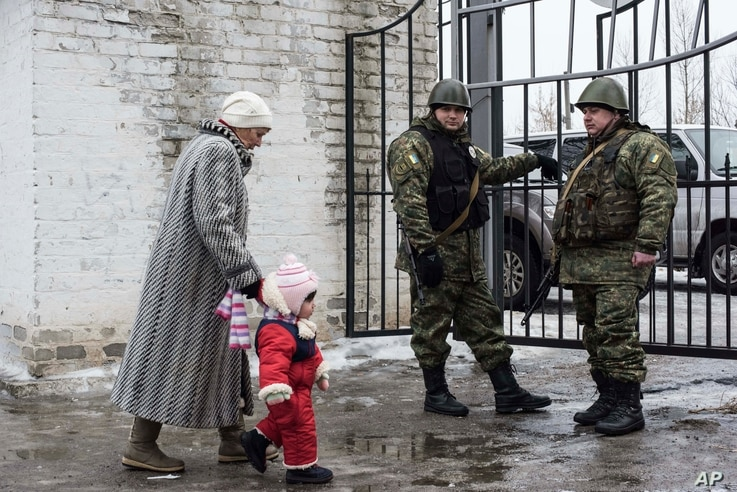 A woman accompanies her child to be evacuated from Avdiivka to Sviatohirsk, a town about 140 kilometers (88 miles) away and far from the conflict front line, in eastern Ukraine, Feb. 5, 2017. A sharp escalation in fighting between Ukrainian troops an...