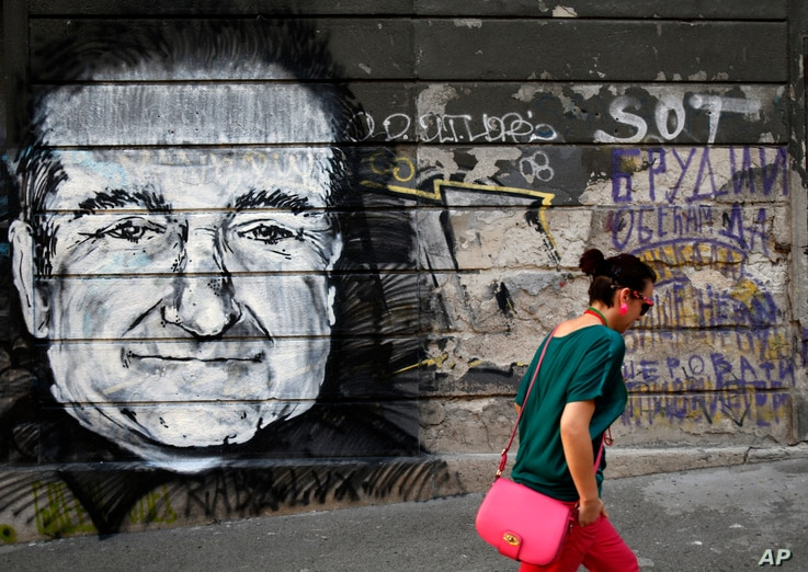 A woman walks past graffiti on a wall that shows late actor Robin Williams after he was found dead at his home in California, in Belgrade, Serbia, Aug. 13, 2014.