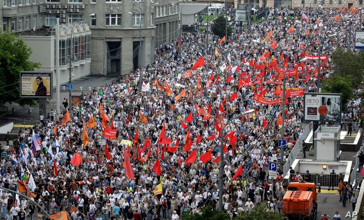 Demonstrators hold the flags of various groups during a massive protest against Putin's rule in Moscow, Tuesday, June 12, 2012. Thousands of Russians are gathering Tuesday for the first massive protest against President Vladimir Putin's rule since hi...