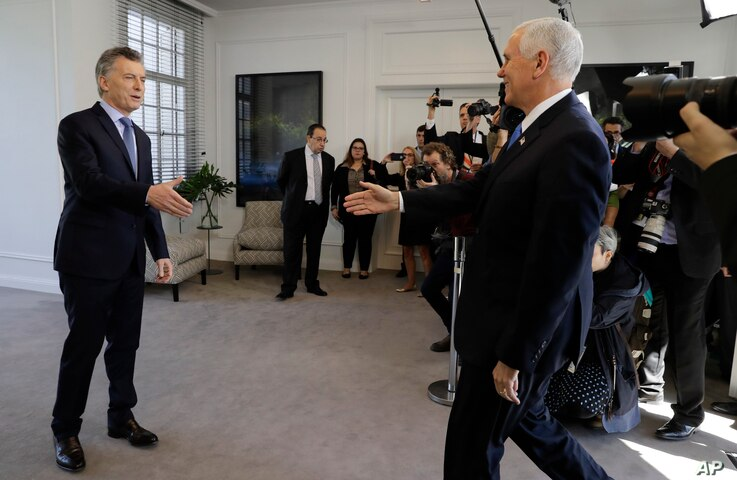U.S. Vice President Mike Pence, right, heads to shake hands with Argentina's President Mauricio Macri at the government residence in Buenos Aires, Argentina, Aug. 15, 2017. Pence is on a official visit to Argentina until Wednesday.