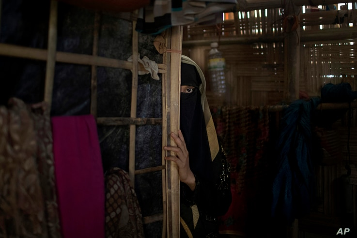 "In this June 26, 2018 photo, ""A,"" a 13-year old Rohingya Muslim girl who agreed to be identified by her first initial, peers from behind a partition in her family's shelter in Jamtoli refugee camp in Bangladesh."