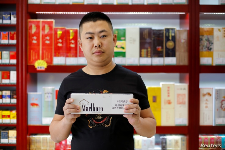 FILE - Shan Yuliang, salesperson at a cigarette and wine shop, poses with a carton of Marlboro cigarettes in Beijing, China, April 8, 2018.