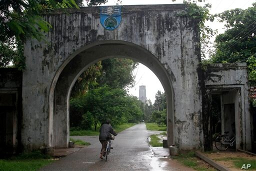 A woman rides a bicycle through the entrance gate of Yangon University in Yangon, Myanmar Thursday, June 28, 2012. The university was once one of Asia's finest and a poignant symbol of an education system crippled by Myanmar's half a century of mil...
