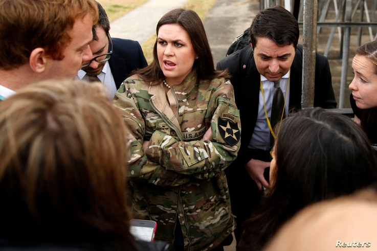 In a borrowed U.S. Army jacket to keep warm, White House Press Secretary Sarah Huckabee Sanders updates reporters on President Donald Trump's failed attempt, preempted by weather, to visit Observation Post Ouellette along the Demilitarized Zone (DMZ)...