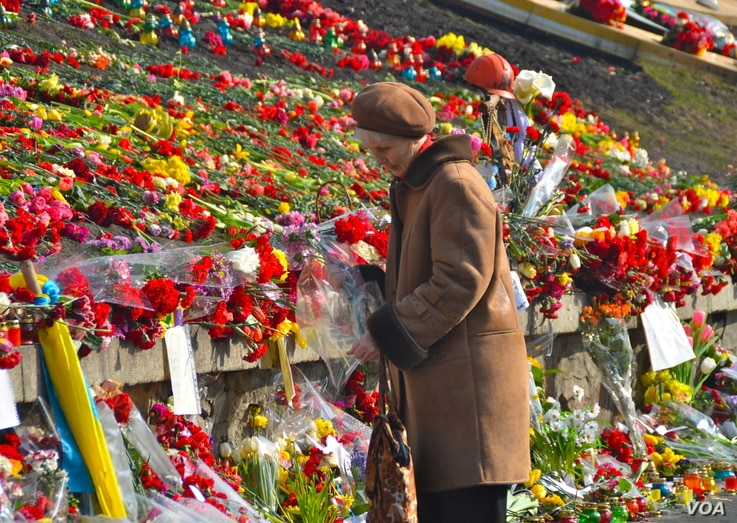 A woman is about to place some flowers and reading the notes on flowers to the dead already laid in Kyiv's Independence Square, Ukraine, Mar. 8, 2014. (Jamie Dettmer/VOA)
