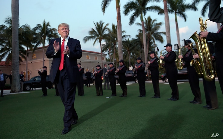 U.S. President Donald Trump listens to the Palm Beach Central High School Band as they play at his arrival at Trump International Golf Club in West Palm Beach, Fla., where he will golf Friday with Japanese Prime Minister Shinzo Abe.