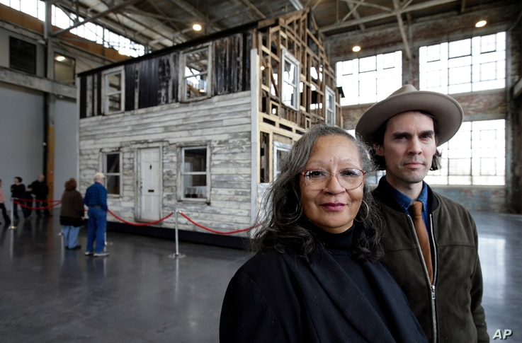 Rhea McCauley, a niece of Rosa Parks, stands for a photograph with artist Ryan Mendoza, April 1, 2018, in front of the rebuilt house of Parks, at the WaterFire Arts Center, in Providence, R.I.