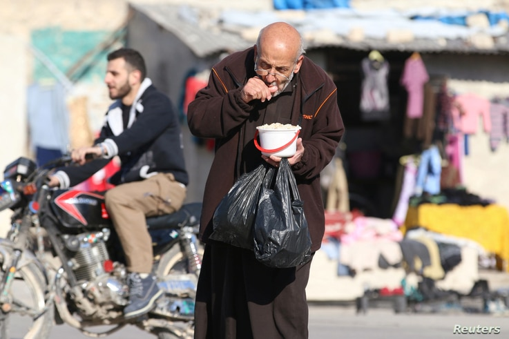 A man eats food that was distributed as aid in a rebel-held besieged area in Aleppo, Syria, Nov. 6, 2016.