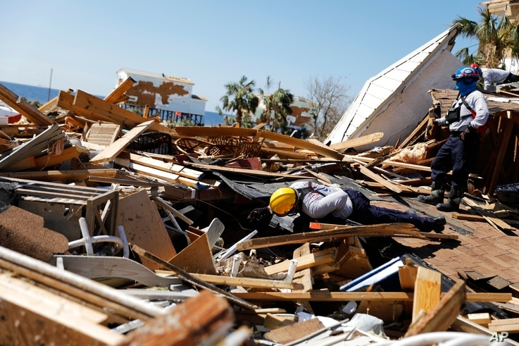 A member of a South Florida urban search and rescue team sifts through a debris pile for survivors of hurricane Michael in Mexico Beach, Fla., Oct. 14, 2018.