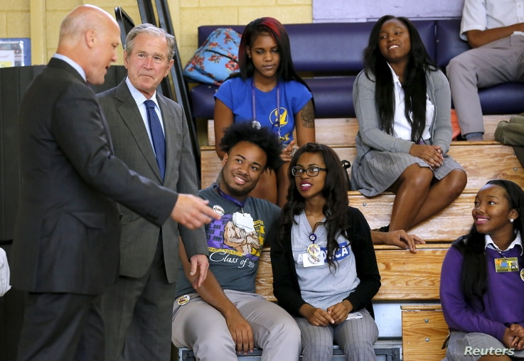 Former U.S. President George W. Bush and New Orleans Mayor Mitch Landrieu (L) talk to students at  Warren Easton Charter High School one day before the ten year anniversary of Hurricane Katrina in New Orleans, Aug. 28, 2015.