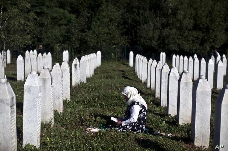 FILE - A woman is seen mourning amid tomb stones at the Potocari memorial complex near Srebrenica, Bosnia and Herzegovina, where victims of the Srebrenica massacre are buried, July 11, 2015.