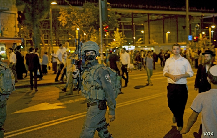 An Israeli special forces soldier walks outside the Central Jerusalem Bus Station after police said a woman was stabbed by a Palestinian outside the bus station, October 14, 2015.