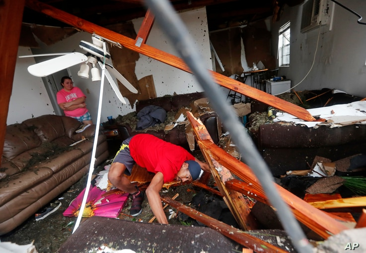 Dorian Carter looks under furniture for a missing cat after several trees fell on their home during Hurricane Michael in Panama City, Fla., Oct. 10, 2018.