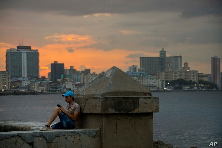 A man chats using his cellphone while sitting on a seawall in Havana, Cuba, Feb. 20, 2019.