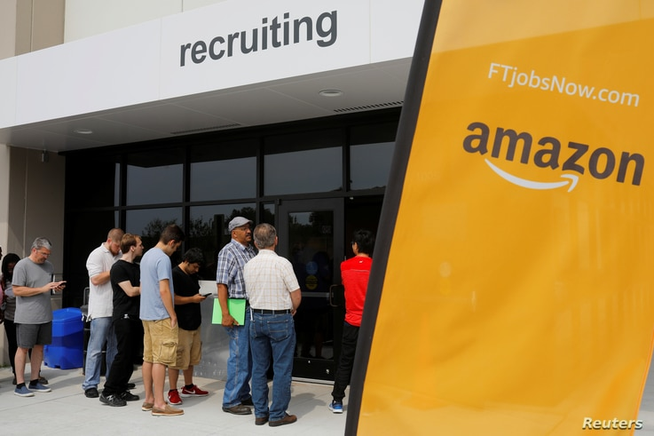 """Job seekers line up to apply during """"Amazon Jobs Day,"""" a job fair being held at 10 fulfillment centers across the United States aimed at filling more than 50,000 jobs, at the Amazon.com Fulfillment Center in Fall River, Massachusetts, Aug. 2, 2017."""