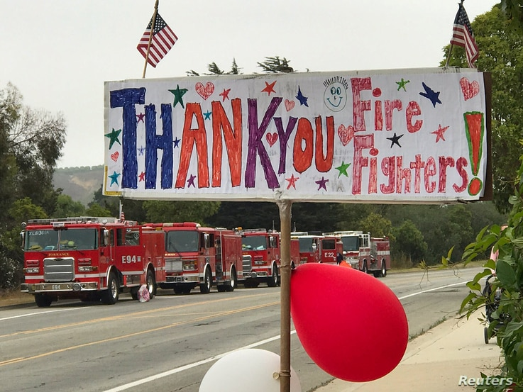 A hand-drawn sign shows thanks to firefighters heading out to tackle the Whittier Fire near Santa Barbara, Calif., July 13, 2017.
