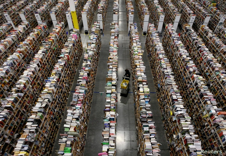 A worker gathers items for delivery from the warehouse floor at Amazon's distribution center in Phoenix, Arizona, Nov. 22, 2013.