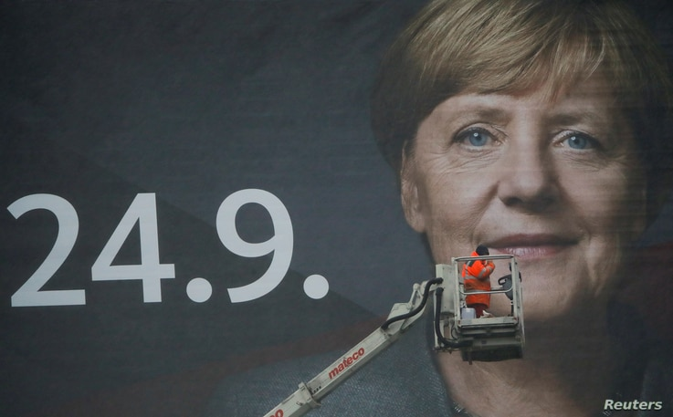 A crane operator steers his mobile crane next to a 18 meters wide 'Mega Poster' of Angela Merkel, German Chancellor and leader of the Christian Democratic Union party CDU after fixing the lights for Merkel's campaign picture.