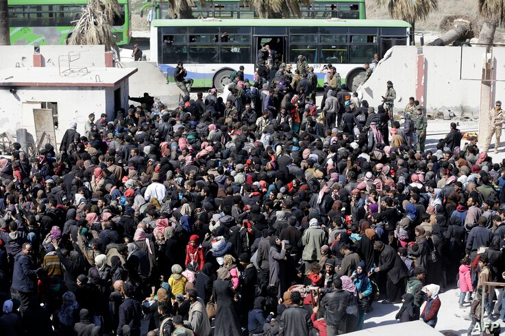 Syrian civilians, evacuated from rebel-held areas in the Eastern Ghouta, gather at a school in the regime-controlled Hosh Nasri, on the northeastern outskirts of the capital Damascus.