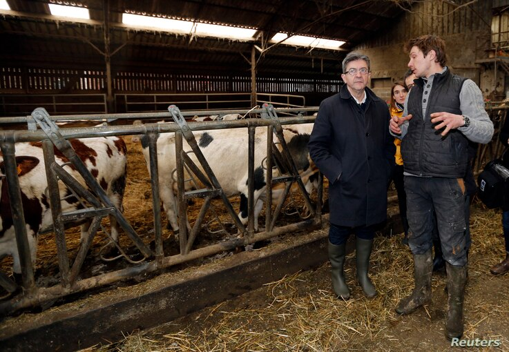 Politician Jean-Luc Melenchon (L), of the French far-left Parti de Gauche, and candidate for the 2017 French presidential election, listens to a farmer during a visit to a farm in Saint-Germain-la-Poterie, France, Feb. 27, 2017.