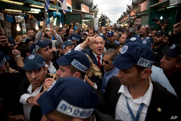 Israeli Prime Minister Benjamin Netanyahu, head of the Likud party, center, is escorted by security guards during a visit to the Ha'tikva market in Tel Aviv, April 2, 2019.