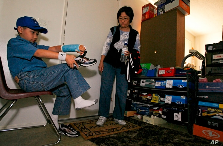 Moshe Kai Cavalin, 10, gets ready for school at home with his mother Shu-Chen Chien in Downey, Calif.