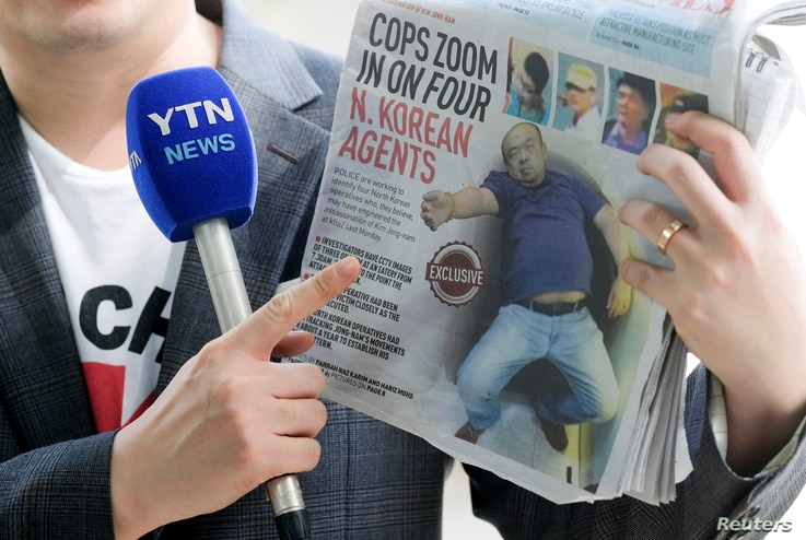 A reporter holds up a local newspaper during his report in front of the morgue at Kuala Lumpur General Hospital where Kim Jong Nam's body is held for autopsy in Malaysia, Feb. 18, 2017.