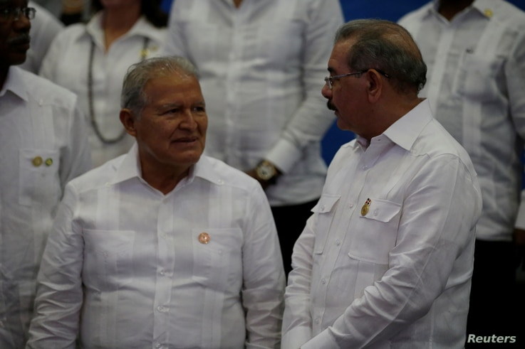 Dominican Republic President Danilo Medina, right, speaks to Salvadorian President Salvador Sanchez Ceren before posing for an official photograph during the Community of Latin American and Caribbean States summit, Jan. 25, 2017.