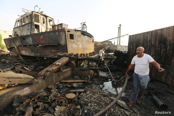 Workers inspect damage at the site of an air strike on the maintenance hub at the Hodeida port, Yemen, May 27, 2018.