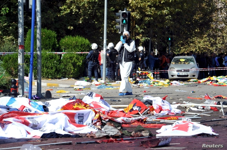 police forensic expert takes pictures as he examines the scene following explosions during a peace march in Ankara, Turkey, Oct. 10, 2015.
