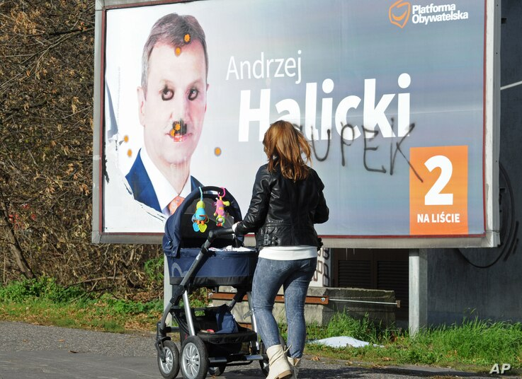 A woman walks past a damaged Civic Platform election poster in Warsaw, Poland, Oct. 26, 2015.