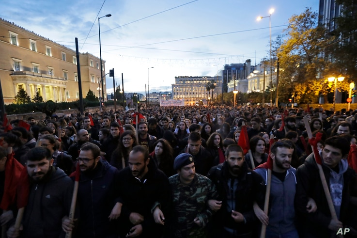 Backdropped by the Greek Parliament, left, demonstrators march in central Athens,Nov. 17, 2017.